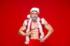 Christmas. Sport, activity. Santa Claus . Young muscular man wearing Santa Claus hat demonstrate his muscles Royalty Free Stock Image