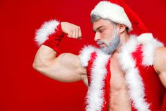 Christmas. Sport, activity. Sexy Santa Claus . Young muscular man wearing Santa Claus hat demonstrate his muscles. On red background Royalty Free Stock Photography