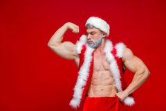 Christmas. Sport, activity. Sexy Santa Claus . Young muscular man wearing Santa Claus hat demonstrate his muscles Stock Image