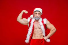 Christmas. Sport, activity. Sexy Santa Claus . Young muscular man wearing Santa Claus hat demonstrate his muscles Stock Images
