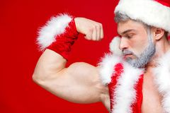 Christmas. Sport, activity. Sexy Santa Claus . Young muscular man wearing Santa Claus hat demonstrate his muscles. Isolated on red background Stock Photos
