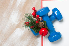 Christmas sport composition with dumbbells, red gift box, berrie. Christmas sport composition with dumbbells, red gift box, red berries, green spruce on plywood stock photos