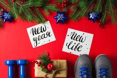 Christmas sport composition dumbbells sneakers new year new life. Christmas sport flat lay composition blue dumbbells sneakers gift box spruce tree branches new stock images