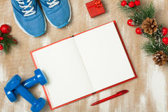 Christmas sport composition with  shoes, dumbbells and note. Christmas sport composition with blue sport shoes, blue dumbbells, red notebook, red small gift box Stock Photography