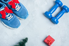 Christmas sport composition with shoes, dumbbells and red gift b Stock Photos