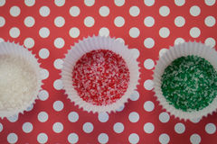 Christmas Sprinkles. Red, green, and white sprinkles in white cupcake papers on a red and white polka dot background Stock Photos