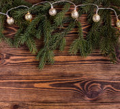 Christmas square composition with vintage garland and fir branches on wooden background. string lights. Stock Photography