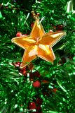Christmas Star. Ornament against green tinsel Royalty Free Stock Images
