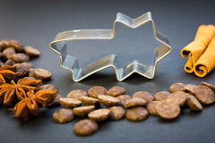 Christmas star cookie cutter and spices. Christmas star cookie cutter, cinnamon sticks, spicy star anise seeds and chocolate on the black background stock images