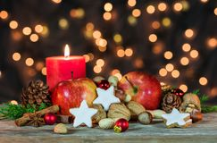 Christmas star cookies, red apples, nuts and spices with festive burning candle Stock Photos