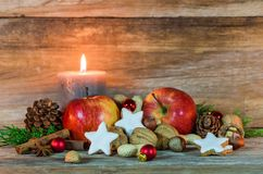Christmas star cookies, red apples, nuts and spices with festive burning candle Stock Image