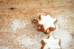 Christmas cookies. Christmas star  cookies and snow from  sugar on vintage wood background - dark moody image of decorative food, simple composition. Card Royalty Free Stock Photography