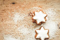 Christmas cookies. Christmas star  cookies and snow from  sugar on vintage wood background - dark moody image of decorative food, simple composition. Card Stock Photos