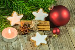 Christmas star cookies, spices, candle, red balls and fir branches stock photography