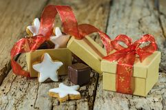 Christmas star cookies and sweet chocolate gift with red ribbon bow on wood royalty free stock photography