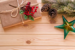 Christmas star, fir tree branch and gift with holly berry. On a wooden background Stock Photography