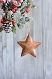 Christmas star hanging on holly berry. Royalty Free Stock Photography