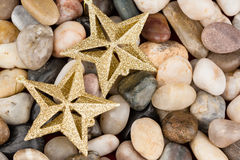 Christmas star ornaments on pebbles Stock Photos