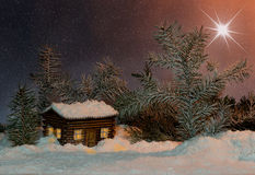Christmas star over the house  in the snow and firs Royalty Free Stock Image