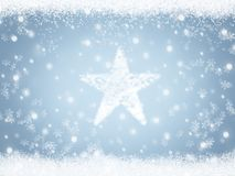 Christmas star from snow on blue winter sky background with snowflakes Stock Photos
