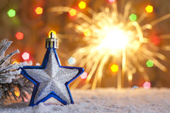 Christmas star on snow and sparklers Stock Image