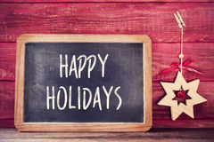 Christmas star and text happy holidays in a chalkboard Royalty Free Stock Images