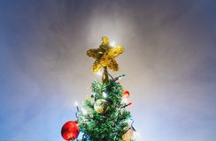 Christmas star on christmas tree with decorations and colorful lights. On soft blue background Stock Photos