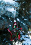 Christmas Star. A triple star Christmas decoration hanging from a snow covered tree branch. Perfect for a Christmas card Royalty Free Stock Image