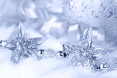Christmas Stars. Sparkling crystal star-shapes, with Christmas balls and ribbon in the background.  White fur and ice-blue tone gives a snowy feel Royalty Free Stock Image