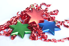 Christmas Stars. Star Christmas tree decorations nestled in red curling ribbon Royalty Free Stock Photo