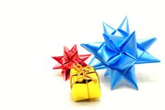 Christmas stars and gold gift. Christmas stars made of red and blue ribbons and gold gift on white background Stock Photo