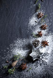 Christmas background. Christmas stars and spices on black stone background Stock Images
