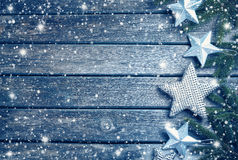 Christmas stars on wooden background with fir tree branches Royalty Free Stock Photo