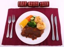 Christmas Steak dinner. Steak dinner with full meal setting and Christmas cracker Stock Images