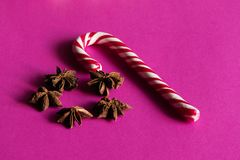 Christmas Stick of hard candy and Star anise spice fruits. And seeds on the pink background.Low angel view.Copy spase for text royalty free stock photography