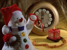 Christmas still life. With a snow man,a clock and a candle Royalty Free Stock Photo