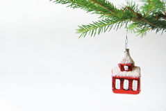 Christmas still life. Christmas decoration, little red house on spruce, isolated on white Royalty Free Stock Photo