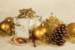 Christmas still life. Christmas still life with cinnamon, pine cone, orange, present and golden christmas balls and decoration Royalty Free Stock Images