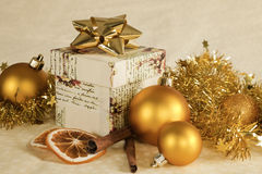 Christmas still life. Christmas still life with cinnamon, orange, present and golden christmas balls and decoration Royalty Free Stock Photos