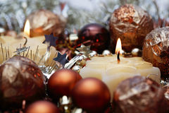 Christmas still-life. Two burning candles and Christmas decorations around, selective focus Stock Image