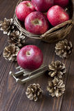 Christmas still life with apples and pine cones. Christmas composition with holiday decoration Stock Photos