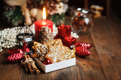 Christmas still life with biscuits. Ornaments, pine cones, wreaths and burning candle on a wooden background Royalty Free Stock Photography