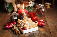 Christmas still life with biscuits. Ornaments, pine cones, wreaths and burning candle on a wooden background Royalty Free Stock Photos