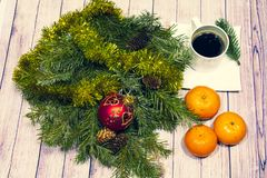 Christmas still life. branches of green spruce with ornaments, a Cup of coffee and tangerines on a light background stock photos