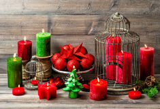 Christmas still life with burning candles and red baubles Royalty Free Stock Image