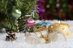 Christmas still life with candle, bells, gift, cone and highlights in the background. Lie on the snow bells and gift. Standing next to a Christmas tree and Royalty Free Stock Photos