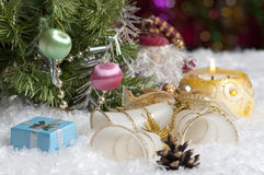 Christmas still life with candle, bells, gift and cone Stock Images