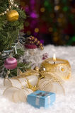 Christmas still life with candle, bells and gift on foreground. Lie on the snow bells and gift. Standing next to a Christmas tree and Santa Claus. A lighted Royalty Free Stock Photography