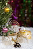 Christmas still life with candle, bells and gift on foreground. Lie on the snow bells and gift. Standing next to a Christmas tree and Santa Claus. A lighted Stock Photos
