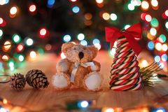 Christmas still life. Candy lollipop in the form of a tree with a red bow, Teddy bear, a pine branch and pine cones on a wooden table on a background of Stock Photo